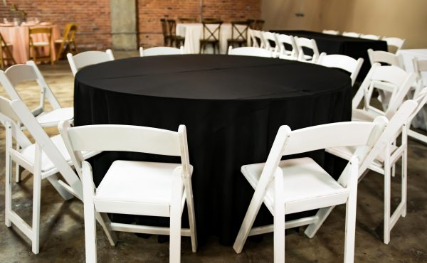 Brick_and_mortar_event_venue_wichita_ks_weddings_indoor_downtown_arena_district_black_tablecloth_white_chairs_basic_setting