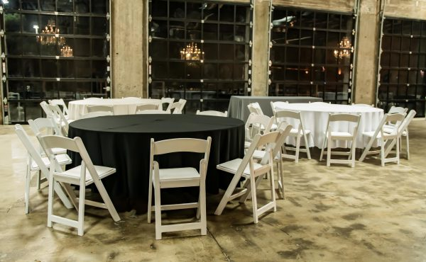 Brick_and_mortar_event_venue_wichita_ks_weddings_indoor_downtown_arena_district_black_tablecloth_white_chairs_basic_settings
