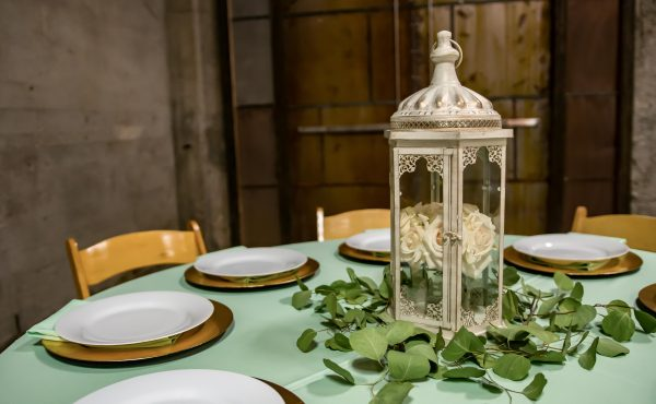 Brick_and_mortar_event_venue_wichita_ks_weddings_indoor_downtown_arena_district_mint_tablecloth_light_wood_stained_chairs_lantern_leaves_table_setting
