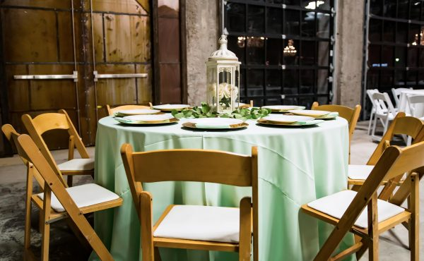 Brick_and_mortar_event_venue_wichita_ks_weddings_indoor_downtown_arena_district_mint_tablecloth_light_wood_stained_chairs_lantern_leaves_white_roses