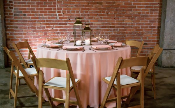 Brick_and_mortar_event_venue_wichita_ks_weddings_indoor_downtown_arena_district_pretty_in_pink_tablecloths_lanterns_gold_accents