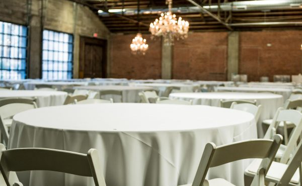 Brick_and_mortar_event_venue_wichita_ks_weddings_indoor_downtown_arena_district_white_tablecloth_white_chairs_basic_setting